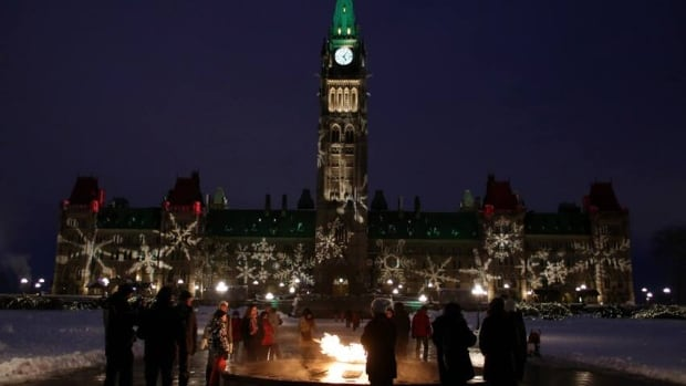 People gather around the Centennial Flame on Parliament Hill in Ottawa on Christmas Eve.