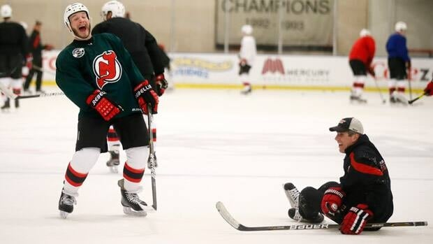 New Jersey Devils' Cam Janssen (L) laughs during a team practice before Game 4 in El Segundo, Calif.