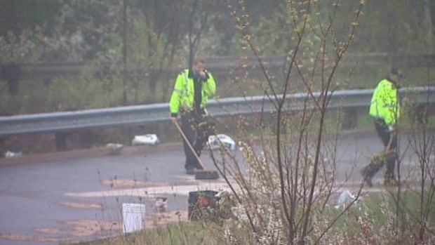 Workers clean up the crash site just off the MacKay Bridge on Friday morning.
