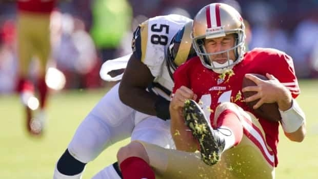 San Francisco 49ers quarterback Alex Smith, right, is tackled by St. Louis Rams linebacker Jo-Lonn Dunbar, left, on Sunday, Nov. 11, 2012, in San Francisco. Smith had a concussion from the play.