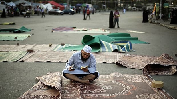 A supporter of deposed Egyptian President Mohammed Morsi reads the Qur'an during a sit-in in Cairo on Wednesday.
