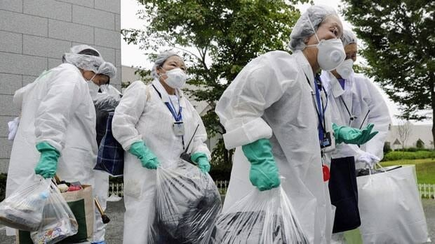 Relatives in protective gear carry belongings of residents in Okuma, the town where the damaged Fukushima Dai-ichi nuclear power plant is located, in Fukushima Prefecture, northeastern Japan.