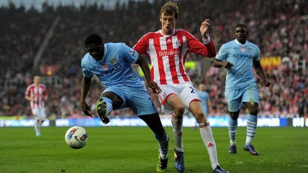 Manchester City's Kolo Toure attempts to clear the ball away from  Stoke's Peter Crouch.