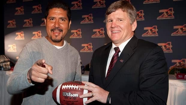 Montreal's star quarterback Anthony Calvillo poses with new head coach Dan Hawkins on Tuesday.