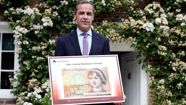 Bank of England governor  Mark Carney poses with the concept design for the new banknote featuring Jane Austen outside the Jane Austen House Museum in Chawton, southern England.