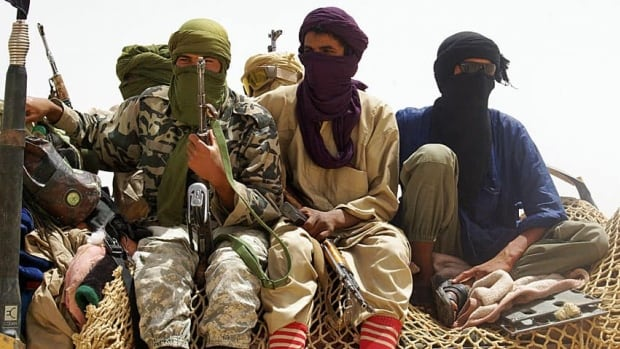 Fighters from Islamist group Ansar Dine stand guard at a designated rendezvous point in the desert outside Timbuktu, Mali. The radical militants continued to destroy ancient tombs designated as UNESCO heritage sites on Monday, amid a growing international outcry.