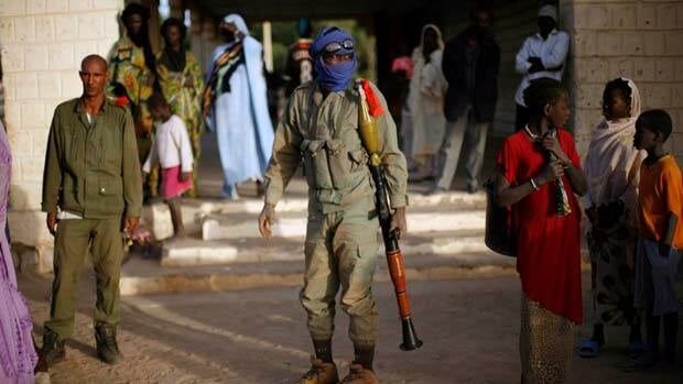 A Malian soldier walks in the street after arriving in a convoy at the military base in Timbuktu on Saturday.
