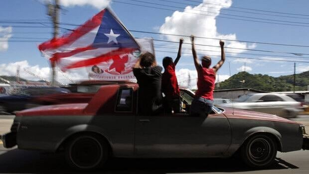 People ride atop a vehicle waving a Puerto Rican flag in San Juan on Nov. 6, 2012. Puerto Ricans voted by a slim margin to become the 51st U.S. state.
