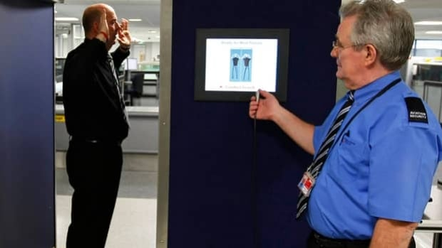 A security official prepares to scan his colleague posing inside a Rapiscan full-body scanner. The U.S. Transportation Security Administration said Friday the X-ray scanners would be removed from airports by June.