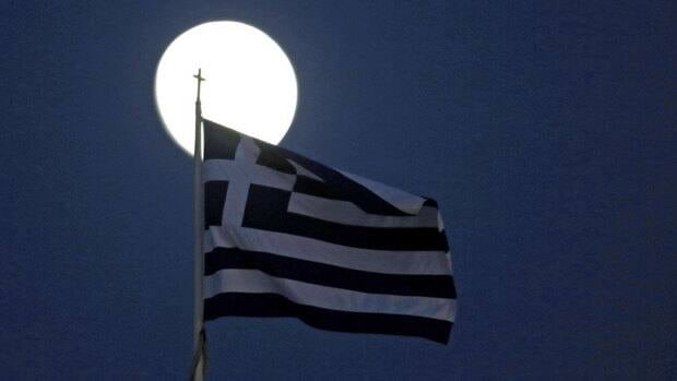 "A Greek flag flutters in front of the moon in Athens. Greek Prime Minister Antonis Samaras hailed the country's new loan agreement as a victory that heralds ""a new day for all Greeks."""