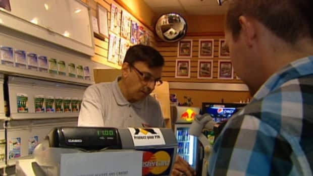 Shiraz Ravji sells a lottery ticket at his kiosk in Edmonton City Centre Mall.