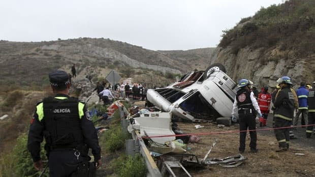 Rescue workers and firefighters stand near the wreckage of an overturned tour bus in Real del Monte, on the outskirts of Pachuca Sunday.