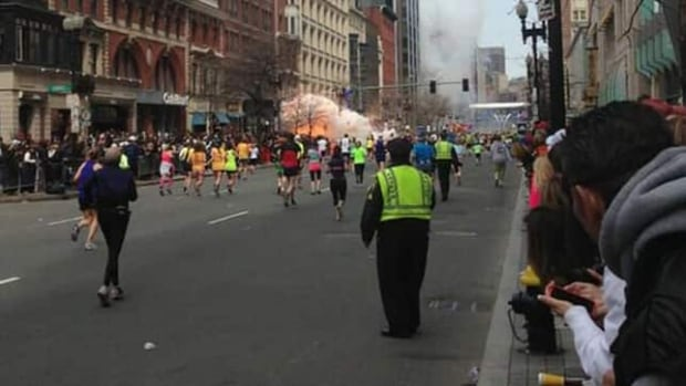 An image captured by Bostonian Dan Lampariello and posted to Twitter shows Boston Marathon runners heading toward the finish line when there's an explosion at street level, and thick smoke rises a block further.