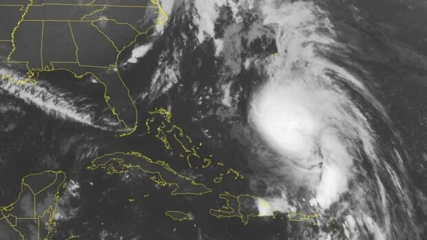 This NOAA satellite image taken Tuesday at 1:45 a.m. ET shows Hurricane Rafael moving northward between Bermuda and Hispaniola.