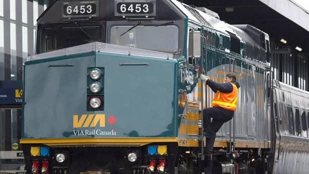 "A Via Rail employee climbs aboard a locomotive at the train station in Ottawa on Monday, December 3, 2012. RCMP say two suspects arrested in an alleged terror attack against a Via Rail passenger train had ""direction and guidance"" from al-Qaida elements in Iran."