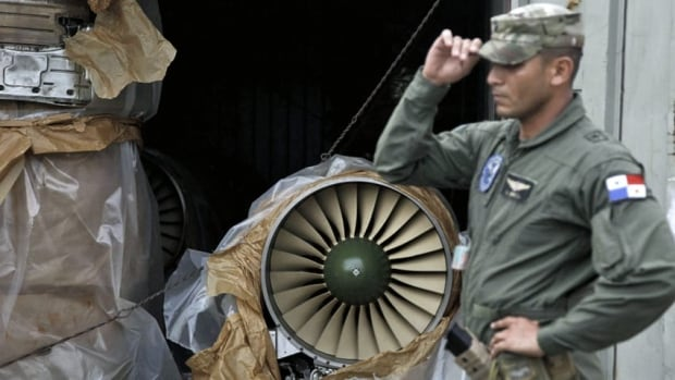 A naval police officer stands in front of a container carrying a Russian-made fighter engine which was taken off the North Korean-flagged freighter ship Chong Chon Gang.