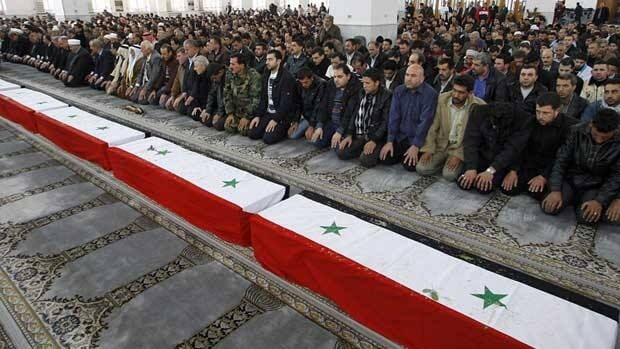 "Syrian mourners pray in front of the coffins of 11 police officers who were killed in an explosion in Damascus on Friday. The government says the blast was the work of ""terrorists"" but opposition groups are calling for an independent investigation into its cause."