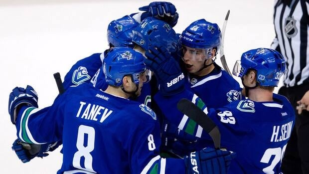Vancouver Canucks' Chris Tanev, from left, Maxim Lapierre, Andrew Alberts, Alex Burrows and Henrik Sedin celebrate Alberts' goal against against the Dallas Stars on Friday night.