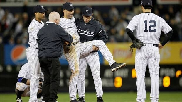 Derek Jeter is helped off the field by Yankees trainer Steve Donohue, second from left, and manager Joe Girardi, second from right, in the 12th inning.