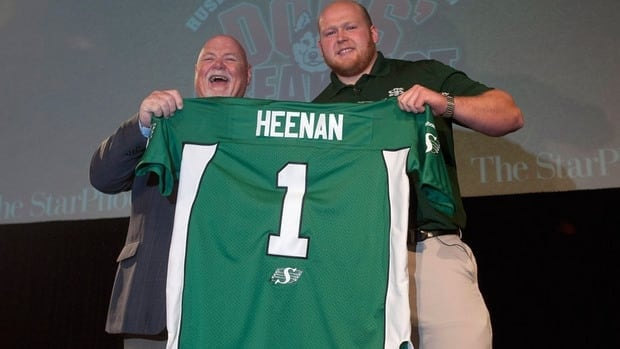 Saskatchewan Roughriders president and CEO Jim Hopson, left, poses Ben Heenan, right, after taking the Huskies offensive lineman No. 1 overall in Thursday's CFL draft.