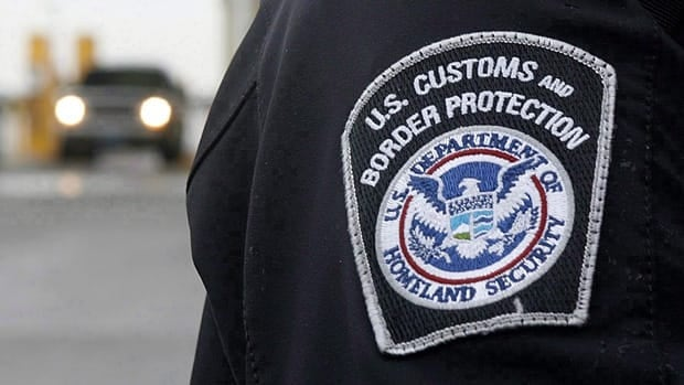 A U.S. Customs and Border Protection officer stands near a security booth as vehicles approach in Detroit, Mich. in 2009. Canada and the U.S. plan to share biometric information about travellers by 2014, newly declassified documents show.