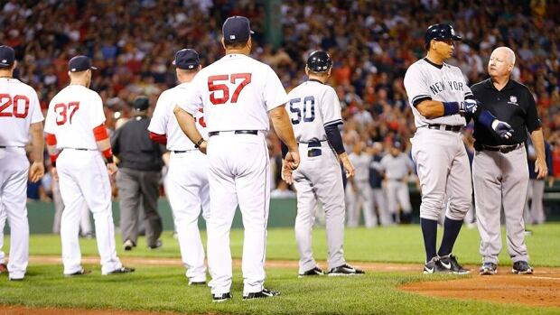Alex Rodriguez, second from right, of the New York Yankees walks to first base with a trainer after being hit by a pitch in the 2nd inning by Ryan Dempster of the Boston Red Sox during the game on Sunday at Fenway Park. Both benches were warned and manager Joe Girardi of the New York Yankees was ejected.