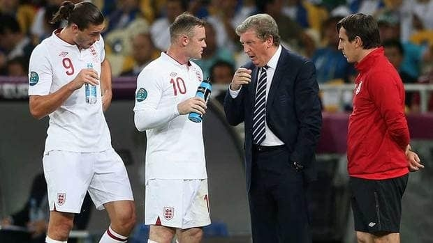 England manager, Roy Hodgson speaks with Andy Carroll and Wayne Rooney during their quarter-final match at Euro 2012 earlier this summer.