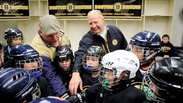 Boston Bruins head coach Claude Julien gets in the the Winthrop, Mass. Squirt B hockey team huddle before coaching them during their game against Watertown in Haverhill, Mass. on Sunday.