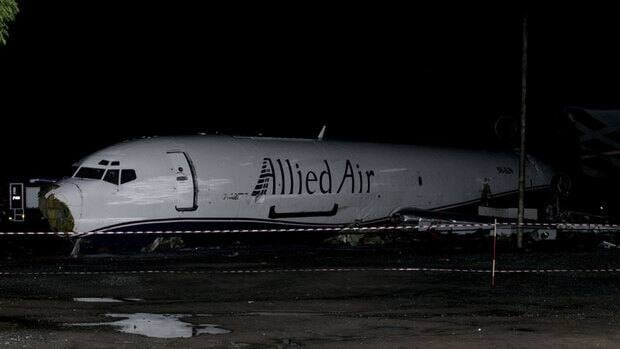 The wreckage of a Boeing 727 cargo plane sits cordoned off on a roadway near Kotoka International Airport in Accra, Ghana, on Saturday after it slammed into a bus.