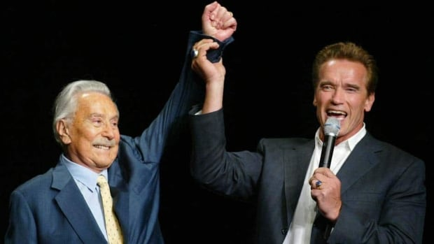 This Oct. 25, 2003 file photo shows then California Gov. Arnold Schwarzenegger, right, raising the arm of Joe Weider, creator of the Mr. Olympia Bodybuilding competition, during the 39th annual Mr. Olympia event in Las Vegas. Weider died Friday at age 93.