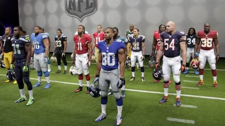 c35f2d5ebb1 NFL players stand in their new uniforms during a presentation in New York  Tuesday. The league and Nike showed off the new look in grand style with a  ...