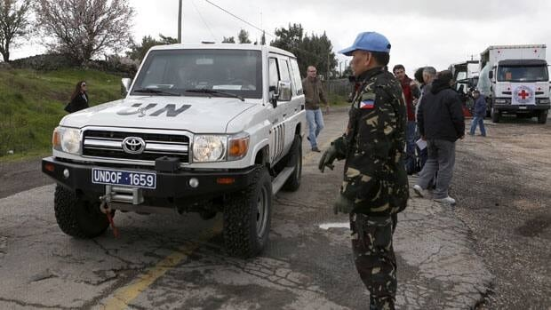 Syrian rebels have seized a convoy of UN peacekeepers near the Golan Heights and say they will hold them captive until President Bashar al-Assad's forces pull back from a rebel-held village which has seen heavy recent fighting.