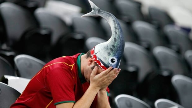 A Portuguese fan sits dejected after the Euro 2012 soccer championship semifinal match between Spain and Portugal in Donetsk, Ukraine on Thursday.