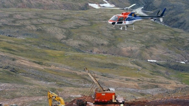 A helicopter passes over excavation equipment at the Mary River exploration camp, the site of a proposed iron mine on northern Baffin Island.