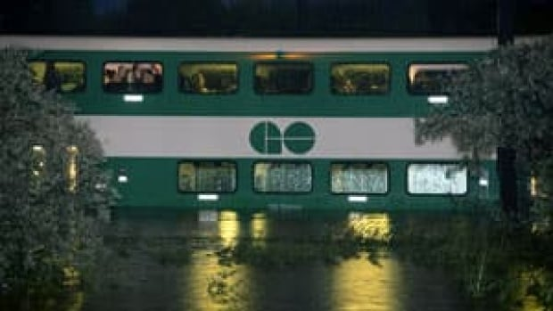 Stranded passengers await rescue on a flooded GO Train in Toronto on July 8. A police officer has been disciplined after posing as one of the rescued commuters for a two-minute TV interview.