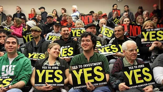 Hamilton residents hold signs for and against a casino at a public forum last week. Coun. Sam Merulla plans to bring up a previous council motion asking for a referendum in 2014. (Samantha Craggs/CBC)