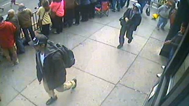 This frame grab from a video released by the FBI on Thursday, April 18, 2013, shows what the FBI are calling suspect number 1, front, in black cap, and suspect number 2, in white cap, back right, walking near each other through the crowd in Boston on Monday, April 15, 2013, before the explosions at the Boston Marathon.