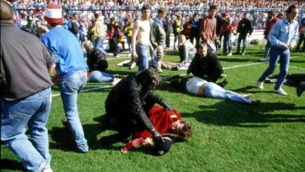 Police, stewards and supporters tend to wounded soccer supporters on the field at Hillsborough Stadium, in Sheffield on April 15, 1989.