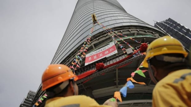 The last piece of the tower is lifted to put in place at the top of the Shanghai Tower during the topping off ceremony in Shanghai, China, Saturday, Aug. 3, 2013. The Shanghai Tower is set to become the tallest building in China which is planned to be complete in 2014.