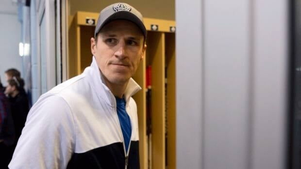 Captain Dion Phaneuf returns to the locker room after talking with the media following an informal Toronto Maple Leafs practice in Toronto on Thursday.