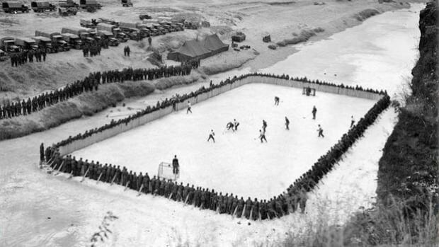 Canadian soldiers line the boards of a makeshift ice rink on the Imjin River in Korea in 1952.