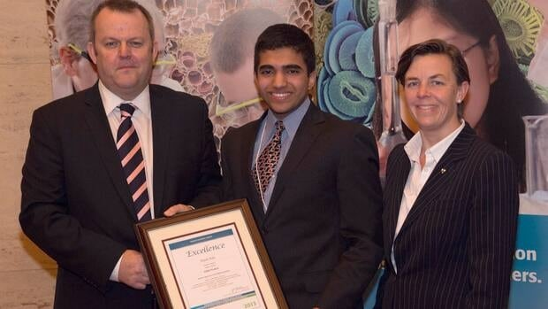 Arjun Nair, 16, of Calgary receives the $5,000 first prize in this year's Sanofi BioGENEius Challenge national competition from Jon Fairest, president and CEO of Sanofi Canada, and Dr. Kellie Leitch, parliamentary assistant to the minister of Human Resources and Skills Development Canada.