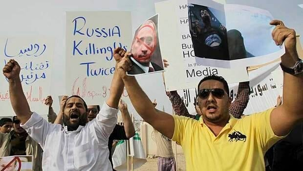 Syrians living in Qatar take part in a protest in front of the Russian embassy in Doha. Qatar and five other Gulf nations withdrew their ambassadors Tuesday.