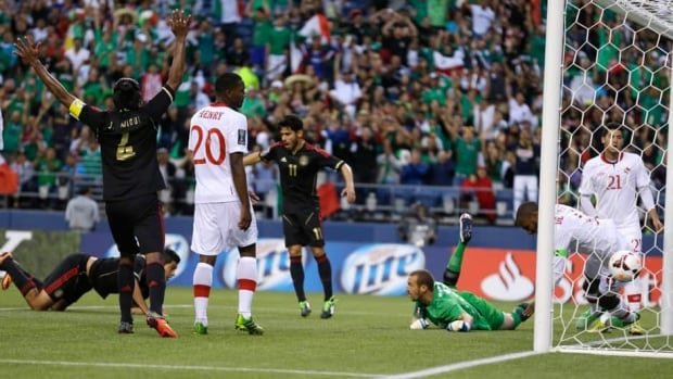 A ball headed by Mexico's Raul Jimenez, lower left, gets past Canada goalkeeper Milan Borjan, third from right, for a goal in the first half of their Gold Cup soccer match Thursday.