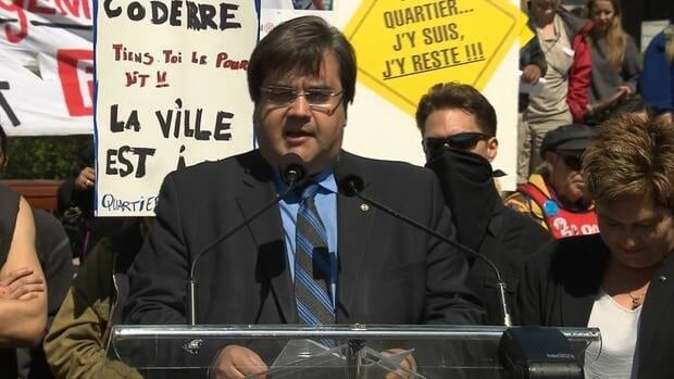 Denis Coderre announces his bid for Montreal's mayoralty against a backdrop of protesters.