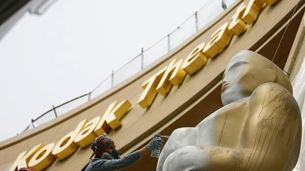 A worker sprays paint on an Oscar statue outside the Kodak Theatre in Hollywood in 2009. The photography company has ended its deal with the Academy Award venue.