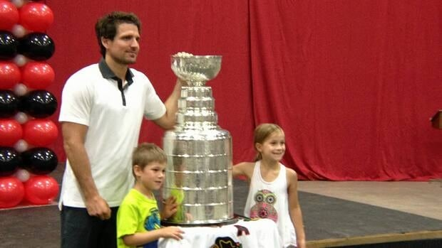 Patrick Sharp poses with the Stanley Cup and a couple of excited fans at the Fort William Gardens in Thunder Bay on Friday