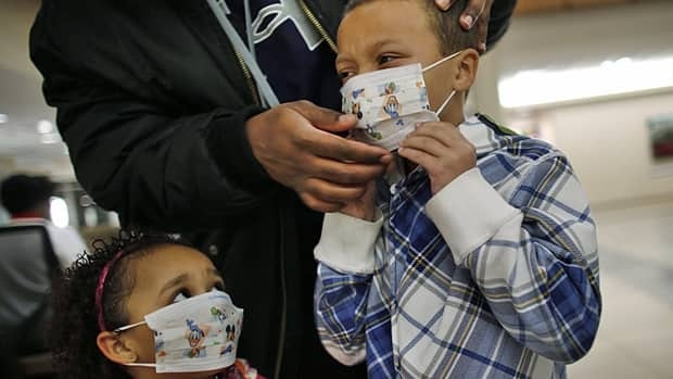 Damien Dancy puts masks on his children Damaya, 3, left, and Damien, 7, on Wednesday at  Sentara Princess Anne Hospital in Virginia Beach, Va. Some U.S. hospitals are turning away visitors or making them wear masks.