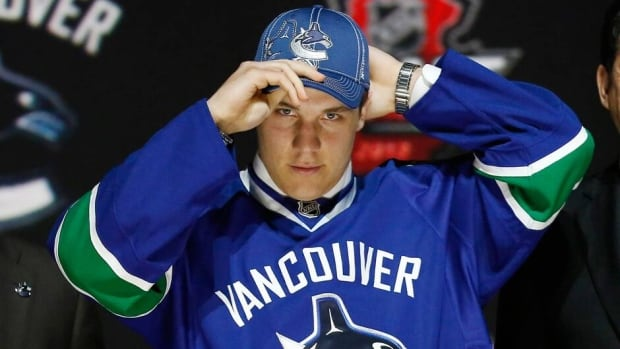 Bo Horvat tries on his Vancouver Canucks jersey and cap after being selected by the Canucks as the ninth overall pick in the 2013 National Hockey league (NHL) draft in Newark, New Jersey, June 30, 2013. REUTERS/Brendan McDermid  (UNITED STATES - Tags: SPORT ICE HOCKEY) - RTX117IW