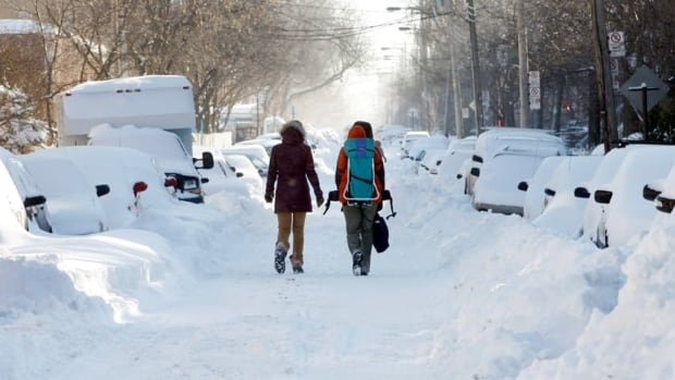 A couple makes its way through snow-covered streets in Montreal after a storm blanketed much of Eastern Canada in December 2007. The storm delivered between 30 and 40 cm of snow and featured winds of 100 km/h in some regions.